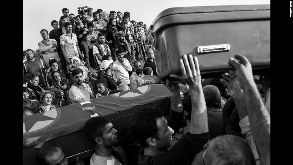 Refugees watch the procession of soldiers being buried in Turkey.