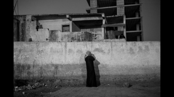 A woman tries to reach someone by phone in a safe zone behind the walls.