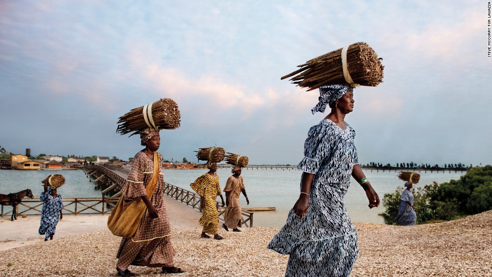 "Anna Ndiaye, pictured front right, is the president of the Gie Mbel Saac Federation in Fadiouth, Senegal. Together with the island's other women, she has devoted herself to the arduous process of preparing the island's prized product: Salted millet cous cous. This variant of cous cous is not grown anywhere else in the world. Like many of the ""Earth Defenders"" captured in this series, these women illustrate clearly the role females can have in harvesting and protecting African products."