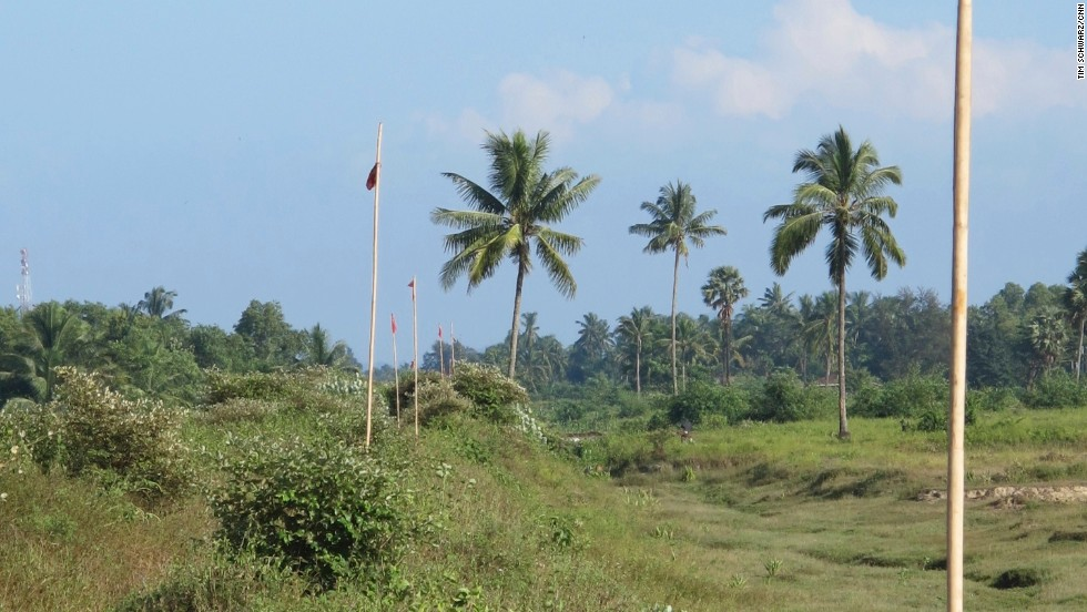 This row of red flags marks a line beyond which Rohingya are not allowed to go. Buddhist Rakhine villages are to the left. There is no barrier or barbed wire stopping people from crossing, but local Muslims fear they would be attacked and killed if they did.
