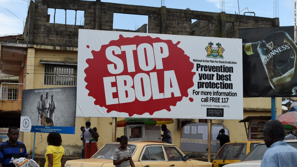 People walk past a billboard with a message about Ebola in Freetown, the capital of Sierra Leone, on November 7. Public awareness campaigns are proving vital in the fight against the virus.
