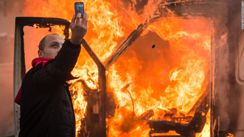 A protestor takes a selfie in front of a burning car in Brussels on Thursday, November 6. Tens of thousands of demonstrators converged on the Belgian capital to protest government policies that will extend the pension age, contain wages and cut into public services.