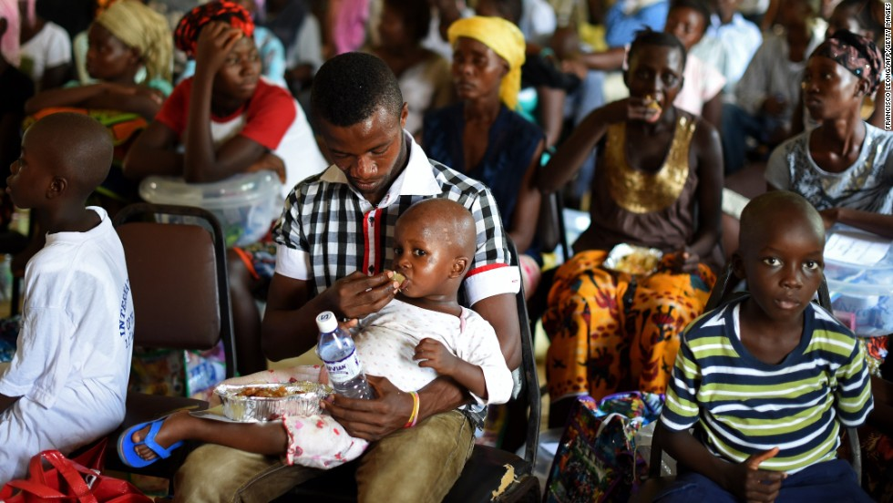 A child who survived the Ebola virus is fed by another survivor at a treatment center on the outskirts of Freetown, Sierra Leone, on November 11, 2014.
