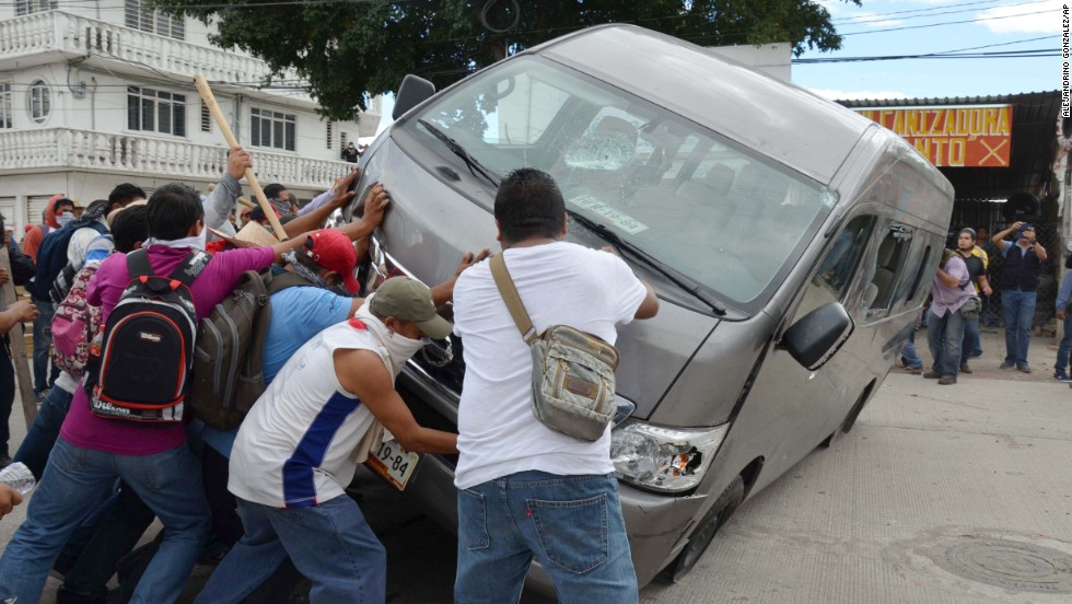Protesters flip a vehicle during a clash with riot police in Chilpancingo on Tuesday, November 11.