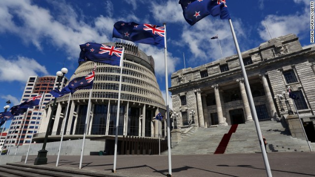 New Zealand flags fly in front of The Beehive and Parliament House in Wellington, New Zealand.