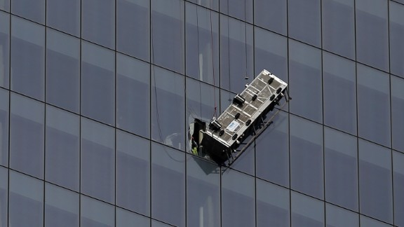 Rescue workers used a diamond saw to tear through three layers of glass panes -- the thickest nearly 2 inches -- in order to pull the workers to safety about 2:15 p.m., authorities said.