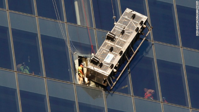 Workers look out at a broken scaffolding that had stranded window washers earlier on the side of 1 World Trade Center in New York November 12, 2014. Two window washers caught on dangling scaffolding on the 69th floor of New York City's 1 World Trade Center were pulled to safety on Wednesday through a window cut in the tallest U.S. skyscraper, a building official said.