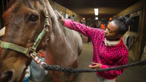 """A young program participant grooms her horse inside a stable at the equestrian center. """"We use horses as a hook to create pride, esteem and healing,"""" Kelly said. """"They learn that they have ability. They just have to unlock it."""""""