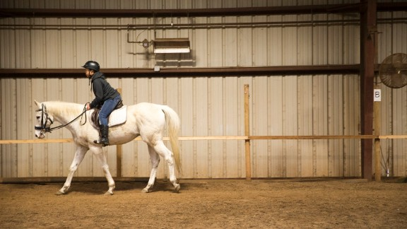 """A child takes riding lessons at the center. """"When you teach a child to ride a horse, they learn they are the center of their environment,"""" Kelly said. """"Once they make that connection, they can change what happens in school, at home and in the community."""""""