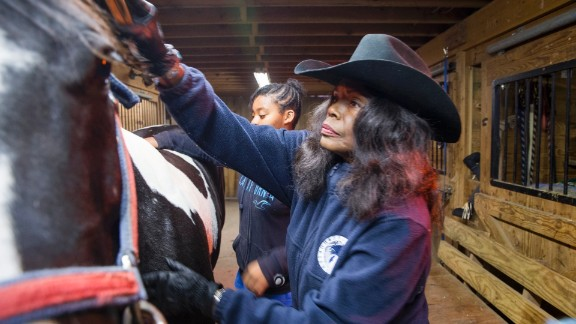 Patricia Kelly grooms a horse on her farm in Hartford, Connecticut. Kelly's nonprofit, Ebony Horsewomen, teaches horseback riding and animal science to at-risk youths, offering them an alternative to the streets.