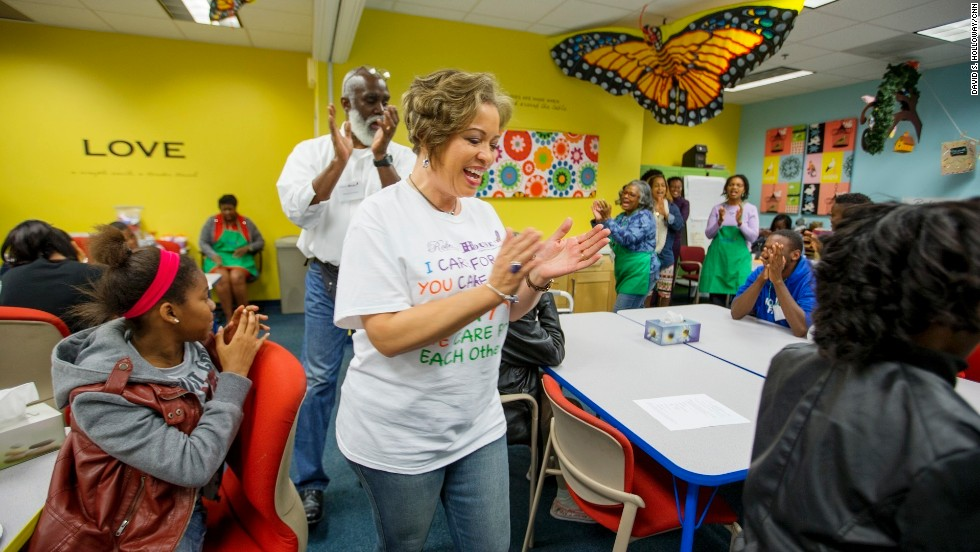 Program participants and volunteers chant at the start of a Roberta's House peer support session in Baltimore. Annette March-Grier, center, founded Roberta's House to help children and their families cope with grief -- particularly the trauma of losing a loved one.