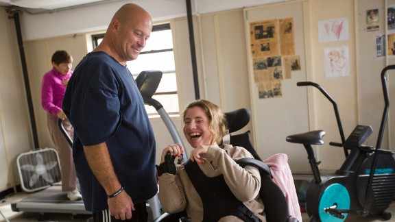 Ned Norton works with a woman at his gym in Albany, New York. For the past 25 years, Norton has provided free and low-cost strength training for people living with disabilities.