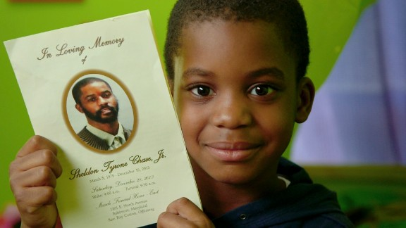 Kyron Chase, 7, holds up a leaflet from his father's funeral. Kyron and his mom have been attending sessions at Roberta's House, and his mom says he is opening up more about his feelings and his dad.