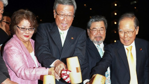 Takeshi Onaga (2nd L) and his supporters open a barrel of awamori, or rice brandy, to celebrate his victory in the Okinawa gubernatorial election on November 16.