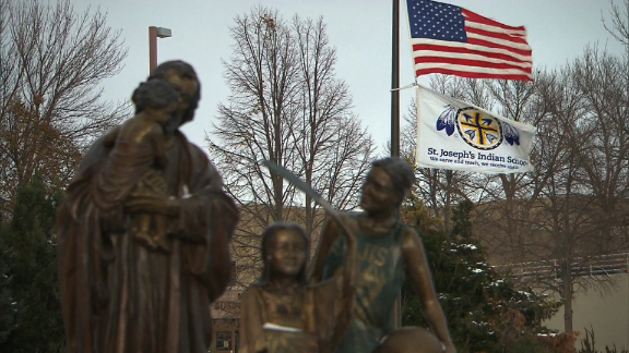 Flags fly at the entrance to St. Joseph