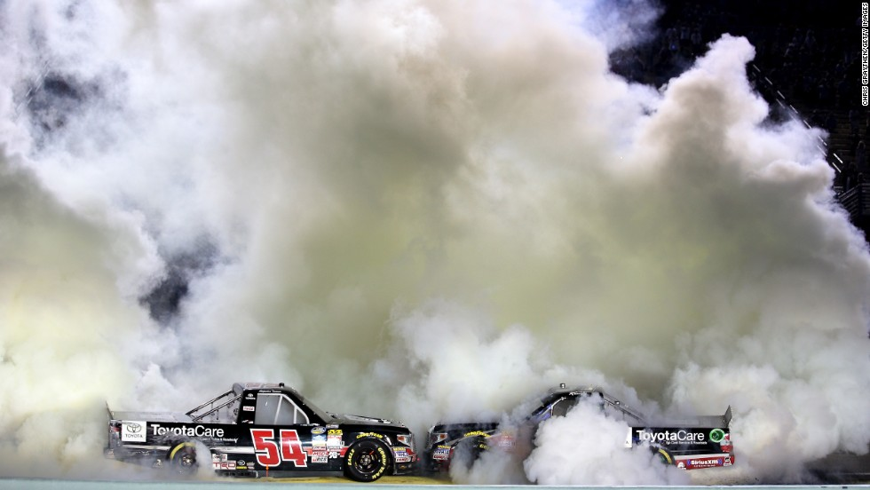 The trucks of Darrell Wallace Jr., left, and Matt Crafton burn rubber at Homestead-Miami Speedway on Friday, November 14. Wallace was celebrating his win in that night's NASCAR Truck Series race. Crafton was celebrating because he won the series championship.