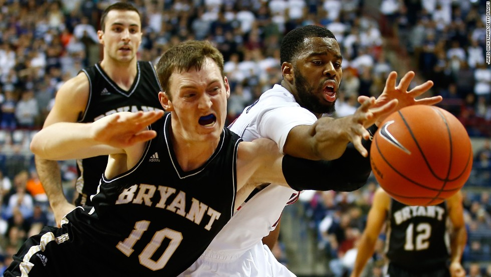 UConn Huskies guard Sam Cassell Jr., right, competes for a loose ball with Bryant's Joe O'Shea during the teams' season-opening game Friday, November 14, in Storrs, Connecticut. The defending champion Huskies won 63-55.