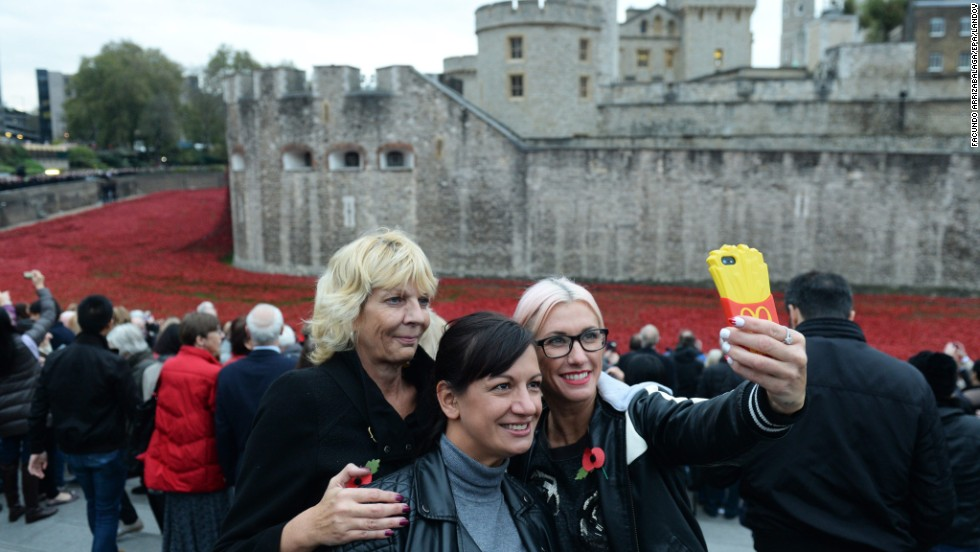 "Visitors pose for a selfie on Tuesday, November 11, the last day of the Tower of London's <a href=""http://www.cnn.com/2014/08/04/europe/gallery/tower-of-london-art-installation/index.html"">ceramic poppy installation.</a> Thousands of ceramic poppy flowers have been installed in the dry moat surrounding the tower to mark the 100th anniversary of World War I. There are 888,246 ceramic poppies, one for each British military member that died during the war. The installation, called ""Blood Swept Lands and Seas of Red,"" was created by artist Paul Cummins."
