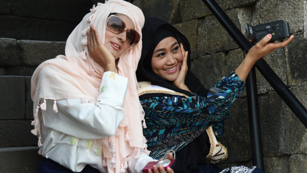Two finalists for the World Muslimah Awards -- Nazreen, left, and Lulu Susanti -- take a picture together while touring the ancient Borobudur temple in Magelang, Indonesia, on Monday, November 17. About 25 women from around the world made the final round of the World Muslimah, a pageant exclusively for Muslim women.