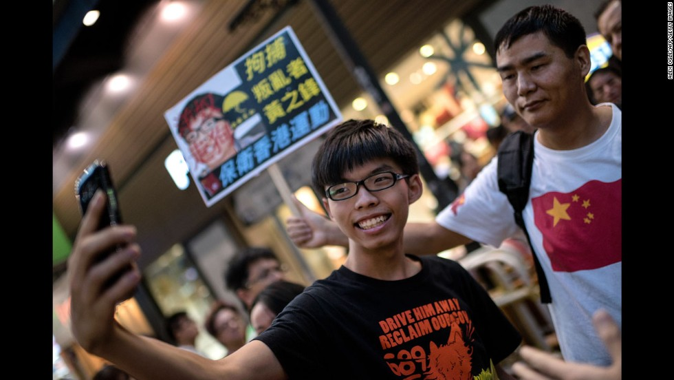 "Student activist Joshua Wong snaps a photo next to a pro-Beijing activist who had been shouting slogans at him while he handed out flyers in Hong Kong on Sunday, November 16. Wong founded the pro-democracy student group Scholarism. <a href=""http://www.cnn.com/2014/09/21/world/asia/hong-kong-joshua-wong-democracy-protest/"">His goal</a> is to pressure China into giving Hong Kong full universal suffrage."