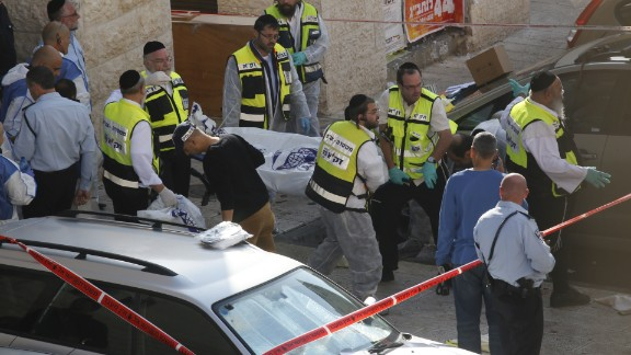 Israeli Zaka emergency services volunteers carry the body of a Palestinian assailant who was shot dead while attacking a synagogue in the ultra-Orthodox Har Nof neighbourhood in Jerusalem on November 18.
