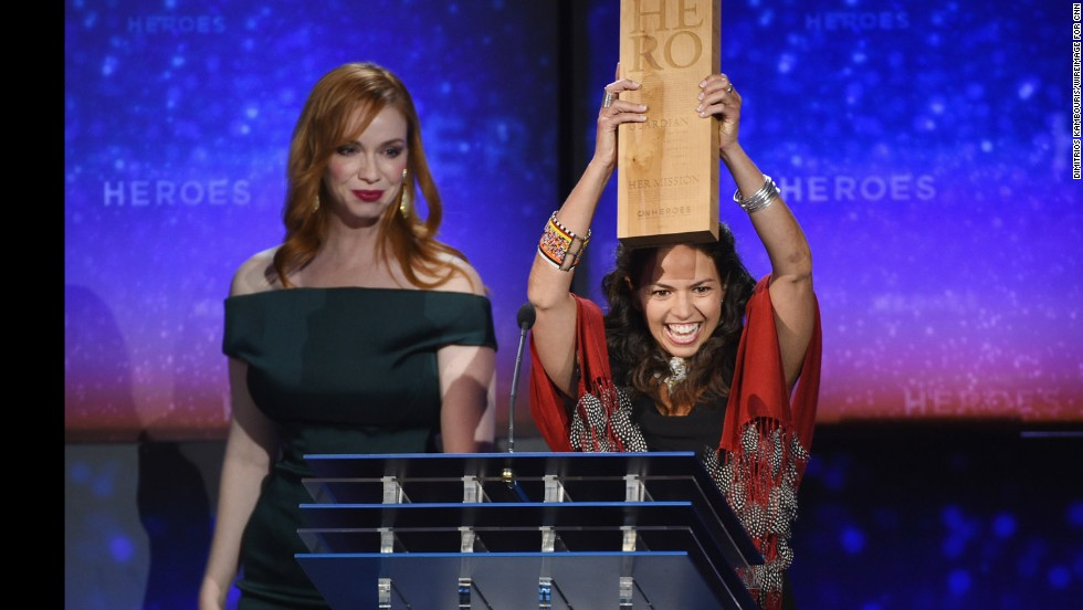 "CNN Hero Leela Hazzah, who is <a href=""http://www.cnn.com/2014/11/24/world/gallery/cnn-heroes-leela-hazzah/index.html"">helping to save lions</a> in Africa, holds up her award next to actress Christina Hendricks during the show."