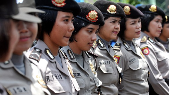 Indonesian policewomen stand guard while Indonesian workers of the All-Indonesia workers union (SPSI) hold a protest against the government