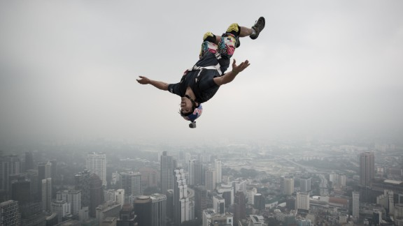 A base jumper leaps from the 980-foot open deck of Malaysia's Kuala Lumpur Tower. Base jumping is an extreme sport in which participants leap from fixed objects and use parachutes to slow their falls.