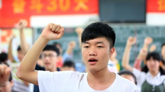 """Students vow to obey the exam regulations before sitting the 2014 college entrance exam of China, or the """"gaokao,"""" in Bozhou, east China's Anhui province. Nearly 10 million high school students sat for China's make-or-break college entrance exams under tight security this year."""