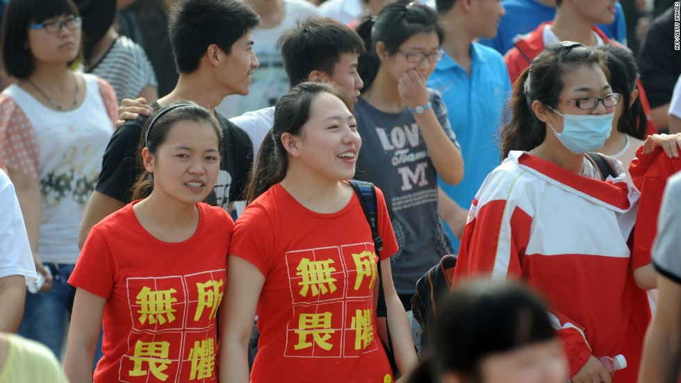 "Two students  wearing t-shirts saying ""fear nothing"" walk into the exam room to sit the 2014 college entrance exam in China, or the 'gaokao', in Bozhou, east China's Anhui province. The ""gaokao"" can make the difference between a prestigious university in Beijing or relegation to a regional college."