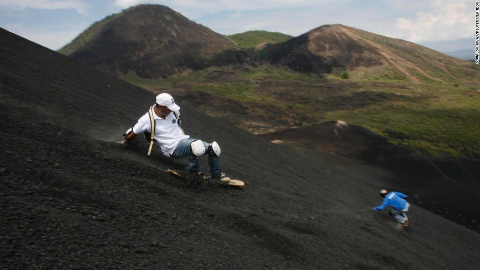 Two men coast down the Cerro Negro volcano in Leon City, Nicaragua. The Cerro Negro is one of Nicaragua's most active volcanoes, and it is a popular spot for the young sport of volcano boarding, or volcano surfing.