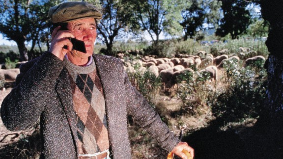 In this 1995 image, a shepherd chats on a flip phone while looking after his flock.