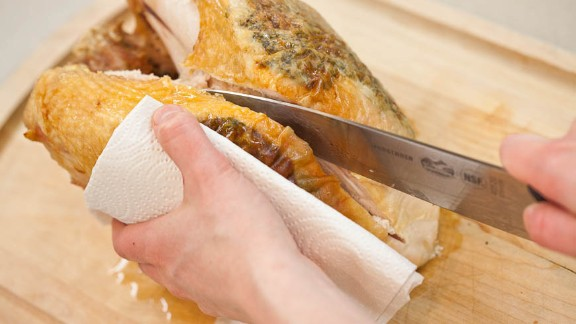 Run chef's or slicing knife along one side of breastbone. Use other hand (with towel to protect it from heat) to pry entire breast half from bone while cutting, being mindful to keep skin intact.