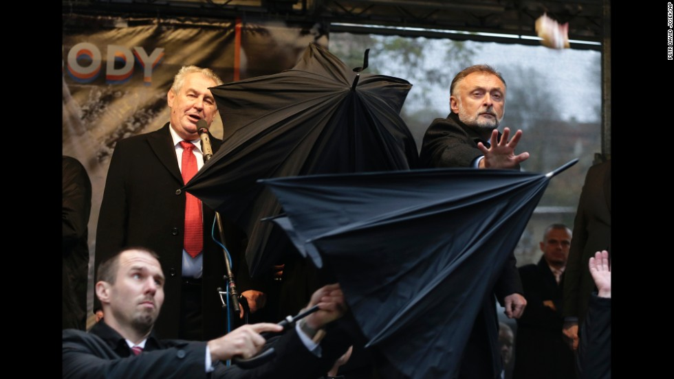 Security personnel use umbrellas to cover Czech Republic President Milos Zeman, top left, during a speech Monday, November 17, in Prague, Czech Republic. During the speech, which commemorated the 1989 Velvet Revolution, protesters booed Zeman and threw objects such as sandwiches, tomatoes and eggs.