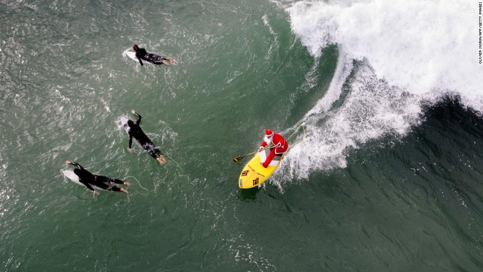 A man dressed as Santa Claus rides a wave in Varazze, Italy, on Tuesday, November 18.