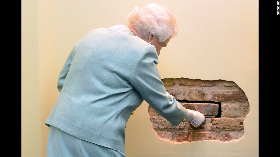 Britain's Queen Elizabeth II removes a brick Tuesday, November 18, during a ceremony in London for the launch of the Queen Elizabeth II Academy for Leadership in International Affairs.