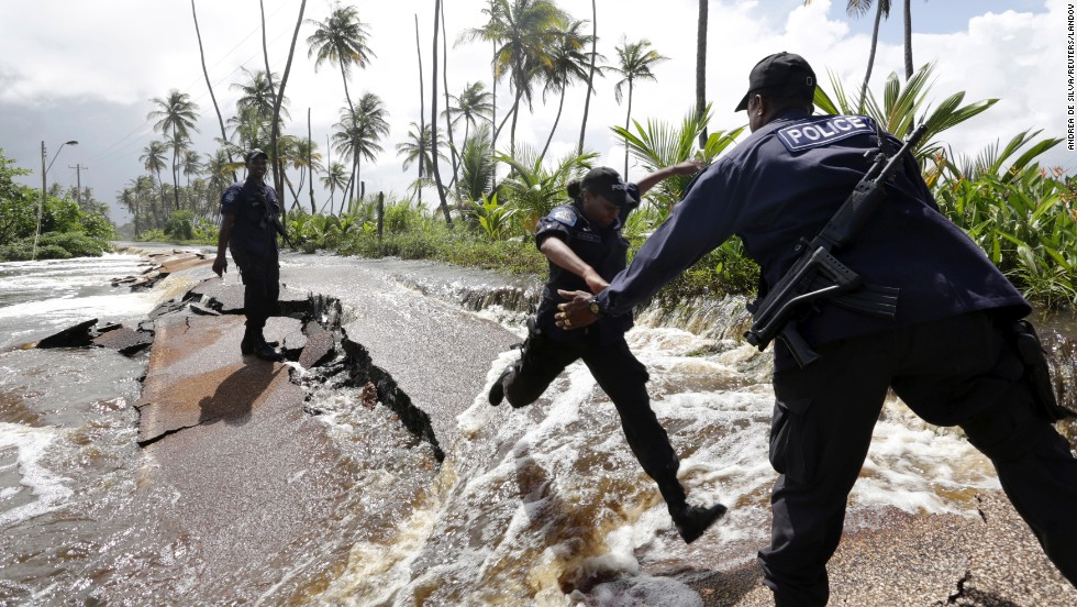 Police Constable Patrice Clarke jumps over a collapsed portion of Manzanilla Mayaro Road as floodwaters continued to flow from the adjoining Nariva swamp Monday, November 17, in Manzanilla, Trinidad.