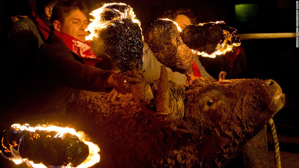 A man restrains a bull as another ignites flammable balls attached to the bull's horns Sunday, November 16, in Medinaceli, Spain. It was for the traditional Toro de Jubilo festival in the town. After the bull's horns are set on fire, the animal is untied and revelers dodge it until the flammable material is consumed. The bull is covered in mud to protect it from burns, but animal rights groups have protested the festival for years.
