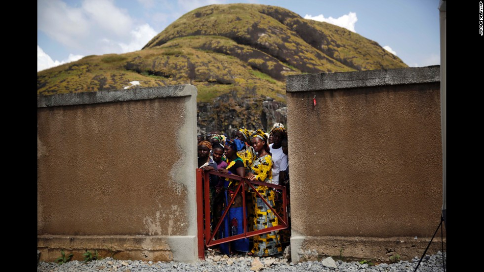 "Residents of Macenta, Guinea, watch the inauguration of an Ebola treatment center there Friday, November 14. The <a href=""http://www.cnn.com/2014/04/04/world/gallery/ebola-in-west-africa/index.html"">Ebola outbreak in West Africa</a> has killed more than 5,400 people, according to the World Health Organization."