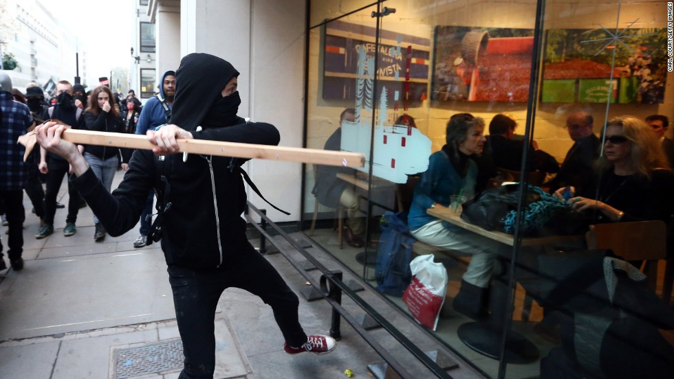 A protester in London tries to smash a Starbucks window Wednesday, November 19, during a demonstration against fees and cuts in the education system.