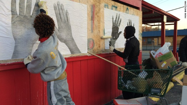 Martez Davis, left, and Anthony Gatling, 19, help put up Damon's art on boarded up Red's Barbecue restaurant.