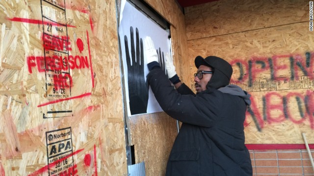 St. Louis artist Damon Davis puts up one of his posters. He wants them to serve as a message of hope for Ferguson.