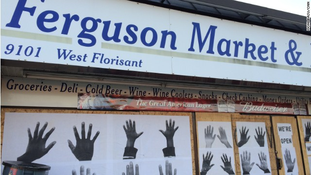 Artist Damon Davis' hands art covers the windows to the convenience store where Michael Brown entered before he was killed August 9.