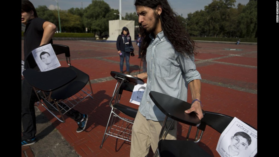 Students place school desks with photos of the missing students in a plaza at Mexico's National Autonomous University on November 20.