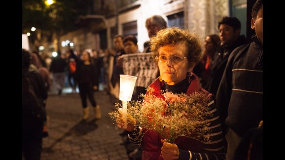 A woman holds flowers and a candle during the November 20 demonstration.