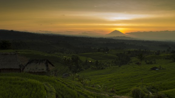 The morning sun warms the Jatiluwih Rice Terrace in Bali, Indonesia. Mount Agung, the highest point on the island, rests in the background.