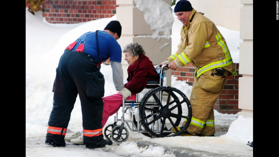 Firefighters from Cheektowaga and Depew, New York, assist an elderly patient from from Garden Gate Health Care Facility to the Appletree Mall November 20. About 180 patients from the facility were moved after officials questioned the safety of the roof under the weight of the snowfall.