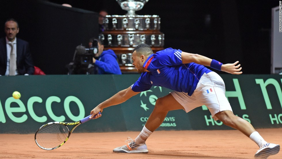 With the giant Davis Cup trophy behind him,  Tsonga stretches to retrieve a shot in going down to Wawrinka