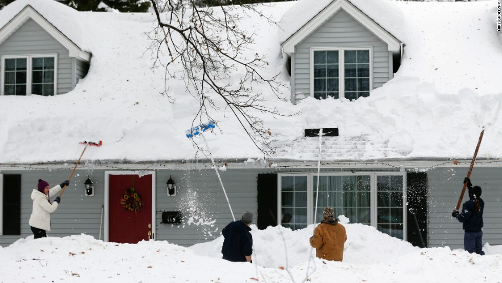 People clear snow from a house on Saturday, November 22 in Orchard Park, New York.