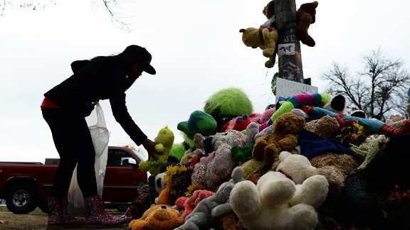 A wellwisher aranges stuffed toys on November 22, 2014 at a makeshift memorial where 18-year-old Michael Brown was shot dead by a police officer, in Ferguson, Missouri. Tensions rose on November 22 in the troubled St Louis suburb of Ferguson, with a grand jury poised to decide whether to prosecute a white police officer for killing an unarmed black teenager. US President Barack Obama has called for calm, Missouri